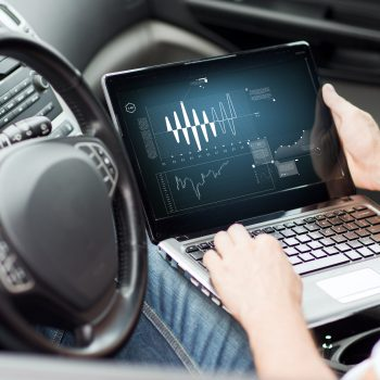 transportation and vehicle concept - man using laptop computer in car